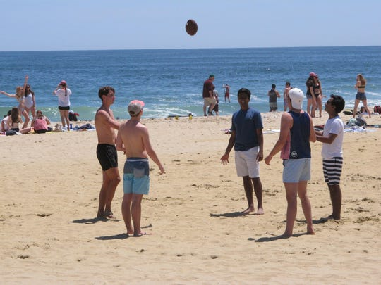This May 21, 2018 photo shows beachgoers playing football on the Belmar, N.J. beach. On May 3, 2019, New Jersey Gov. Phil Murphy signed a law protecting the public's right to access and use the state's waterways and adjacent shorelines.
