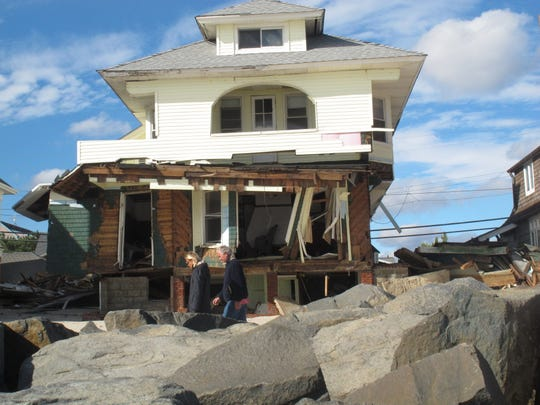 People walking past boulders in Bay Head that were exposed when Sandy washed away the sand that had been atop the rocks.