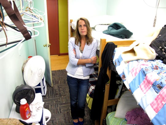 In a dorm room with the meager belongings of homeless guests, Valerie Brosseau, executive director of ANEW Place (formerly Burlington Emergency Shelter), listens to a visitor's questions.