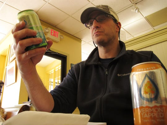 Aaron Harris, co-founder of Fairfield-based TreTap, reads the ingredient label on his company's cucumber-flavored carbonated beverage, made with water drawn from maple trees.
