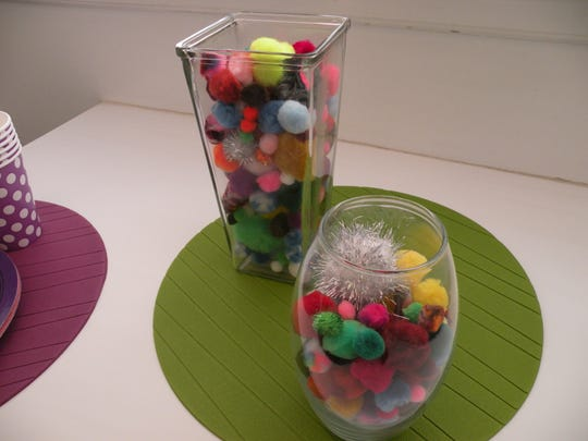 Filling jars with pom poms makes an easy and eye-catching centerpiece.