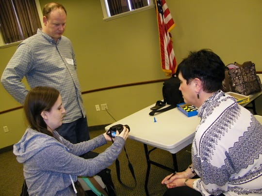 Jonathon Gruneich, Brittany Reardon and Carolyn Farrar discuss the bokeh technique during a meeting of the Clyde Photography Club at the Clyde Library.