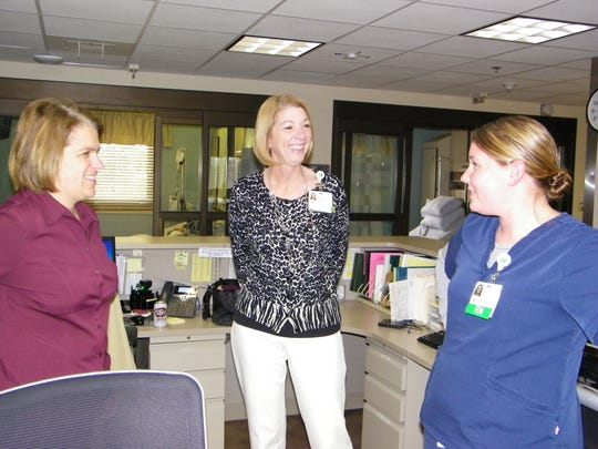 Left to right, Dr. Jennifer Brown, ProMedica Memorial Hospital President Pam Jensen and Jessica Haralson, RN, share a light moment in the intensive care unit of the hospital.