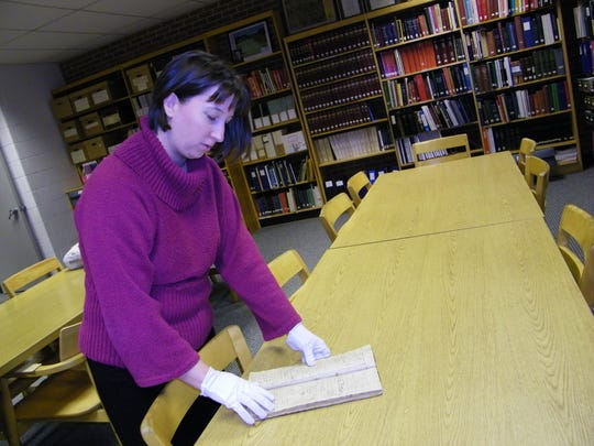 Jen Fording, the local history librarian at Harris-Elmore Public Library, looks through the 1834 ledger of Ezekiel Rice, one of the founders of Elmore.