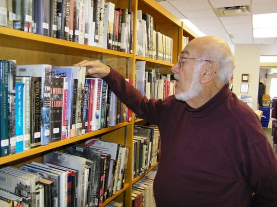Cliff Brooks looks through books on World War II at Harris-Elmore Public Library. Brooks served in the Pacific during the war and then went on to career as a NASA photographer