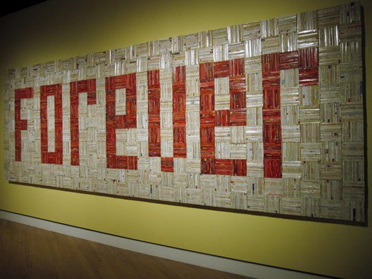 """A solid wall of 4,000 paperback romance novels spelling out the word """"forever"""" is part of an installation at Crystal Bridges Museum of American Art in Bentonville, Ark."""