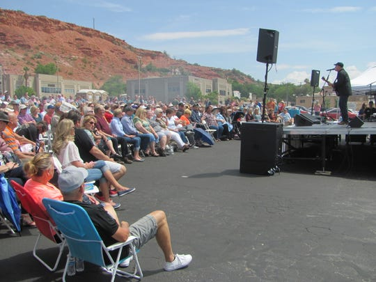 Hundreds of people listen as country musician Collin Raye talks about his career and pays tribute to music legend Glenn Campbell, who is suffering the debilitating effects of Alzheimer's disease. The free parking lot concert was provided by Town & Country Bank behind the St. George Boulevard business's branch office.
