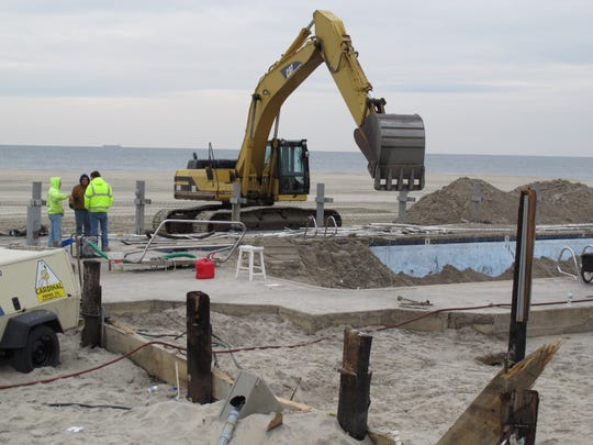 Work crews scoop sand from a beachfront swimming pool in Sea Bright in this January 2013 photo.
