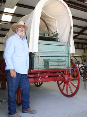 Dave Harkness poses with the 100-year-old chuck wagon that he restored for the New Mexico Farm & Ranch Heritage Museum. A birthday celebration for the wagon, with free Dutch-oven biscuits and cowboy coffee, is part of the festivities on Community Appreciation Day, Aug. 26.