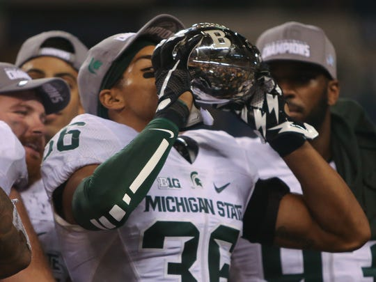 Michigan State Spartans Arjen Colquhoun kisses the Big Ten Championship trophy after the 16-13 win against the Iowa Hawkeyes on Saturday, December 5, at Lucas Oil Stadium in Indianapolis Indiana.