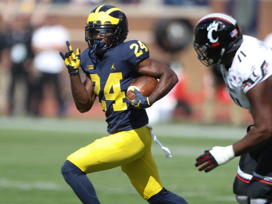 Michigan's Lavert Hill runs back an interception for