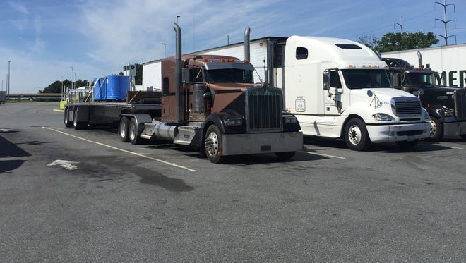 A flatbed truck driven by Kevin Wilhelm of Pennsylvania sits parked at the Delaware Welcome Center Travel Plaza on I-95. Federal officials proposed a rule Wednesday to slow down tractor-trailers and buses.