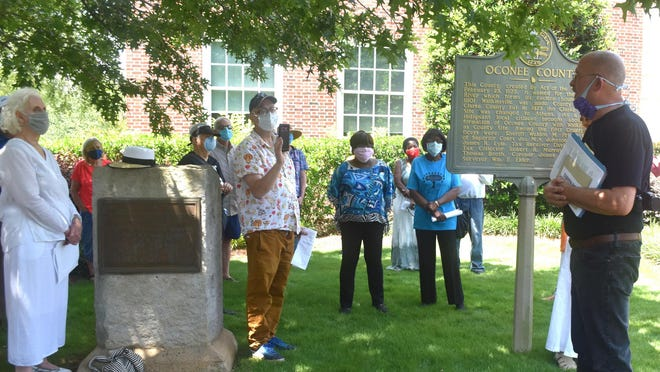About 100 people gathered in Watkinsville Monday for an anniversary vigil remembering eight men lynched by a mob in the town on June 29, 1905.