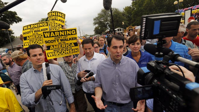 Republican presidential candidate, Wisconsin Gov. Scott Walker is followed by protestors during a visit to the Iowa State Fair, Monday, Aug. 17, 2015, in Des Moines, Iowa.
