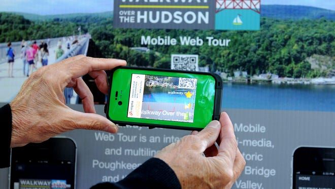 Kathy Smith, former IBM corporate vice president of company transformation, shows how scanning a quick response code on a smartphone at one of the signs, along the Walkway Over the Hudson provides the user a range of information via a mobile Web tour of the state park.