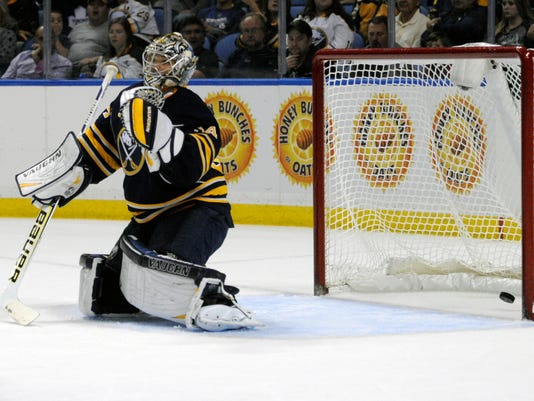 Buffalo Sabres goaltender Michal Neuvirth reacts as he misses the puck for a goal by Toronto Maple Leafs Roman Polak during the second period of an NHL hockey preseason game, Friday, Sept. 26, 2014, in Buffalo, N.Y. (AP Photo/Gary Wiepert)