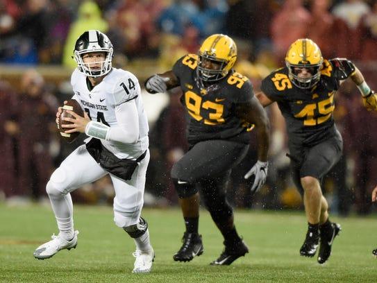 Michigan State quarterback Brian Lewerke keeps his eyes downfield as he scrambles last week at Minnesota.