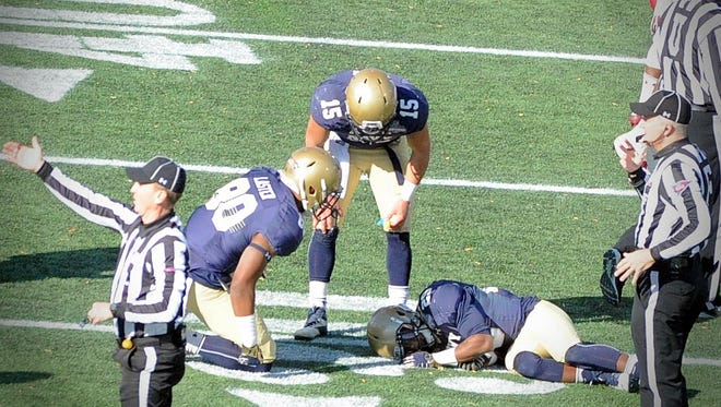 Navy's Will Worth (15) and Terrence Laster (80) check on an injured Darryl Bonner in the American Athletic Conference Championship game on Saturday, Dec. 3, 2016, at Navy-Marine Corps Memorial Stadium.