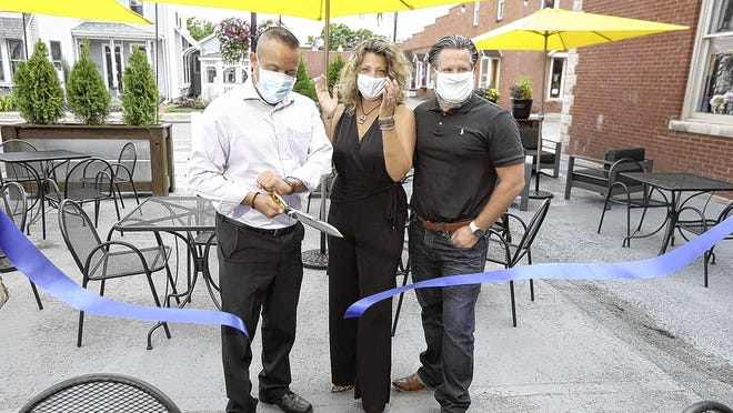 Barrel & Boar owners Jason Woffenden (left) and Cristi and Stan Riley cut a ribbon Aug. 6 to open the temporary patio created in the privately owned parking space the restaurant is leasing behind its building, 8 N. State St. Barrel & Boar is the first restaurant to take advantage of a temporary patio permit by the city of Westerville.