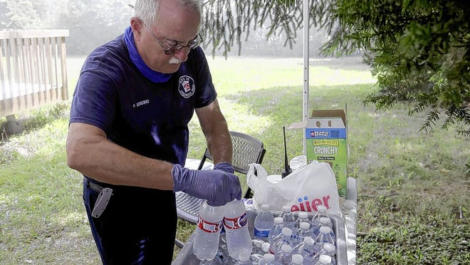 Box 15 rehabilitation specialist Patrick Mignogno restocks bottled water for Jackson Township firefighters during a fire-training session Aug. 11 in Grove City. The volunteer-run Box 15 provides on-site material support to firefighters working active fires or emergency scenes.