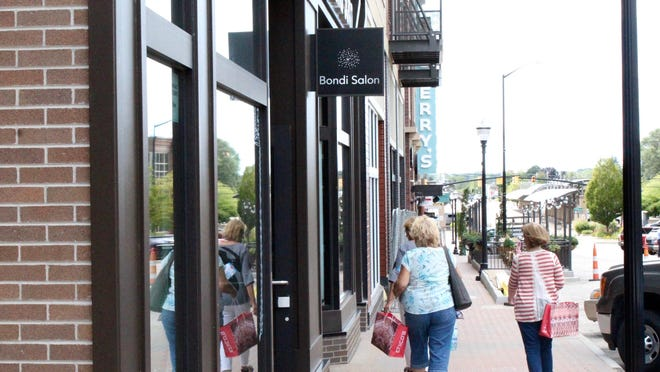 Shoppers walk along the new GDK development on Eighth Street in downtown Holland in August 2019.