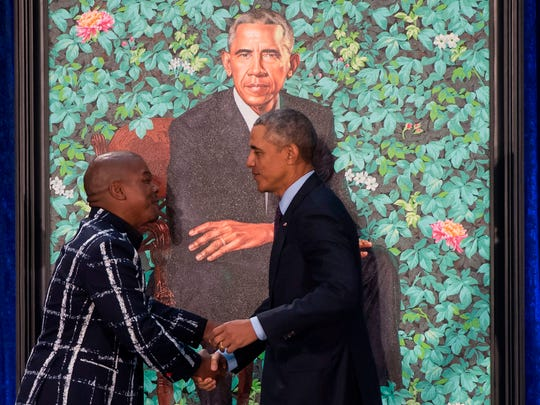 Former President Barack Obama shakes hands with his portrait's artist, Kehinde Wiley, after its unveiling at the Smithsonian's National Portrait Gallery in Washington on Feb. 12, 2018.