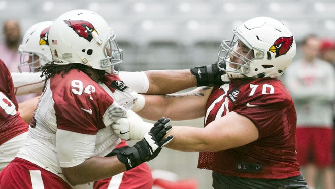 Cardinals defensive tackle Xavier Williams (left) and center Evan Boehm go against each other during a Cardinals' training camp practice at University of Phoenix Stadium in Glendale on Wednesday, Aug. 10, 2016.