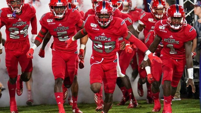 Florida Atlantic cornerback Chris Tooley (26) and teammates run out of the tunnel before a 37-7 victory against FIU on Nov. 9, 2019.