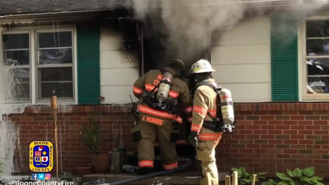 Firefighters enter a home at 6000 N. Vicki Drive on Tuesday. A resident, George Williams, has been charged with arson in connection with the blaze.