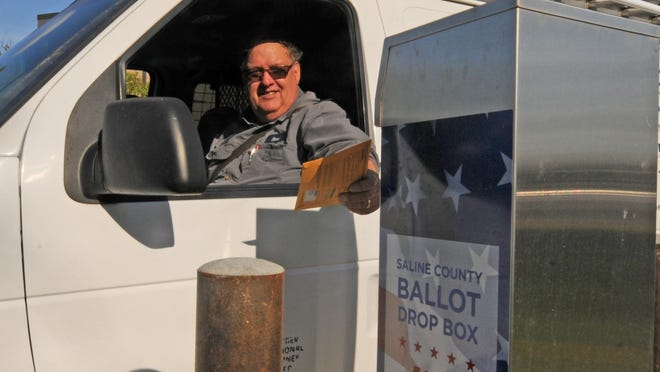 """Steve Miles, of Salina, drops off his ballot in the ballot drop box in the circle driveway of the City-County Building, 300 W. Ash St., on Thursday. """"It is easy just to drop it off. I am a working man, so it is hard to take off sometimes when I need to,"""" Miles said."""