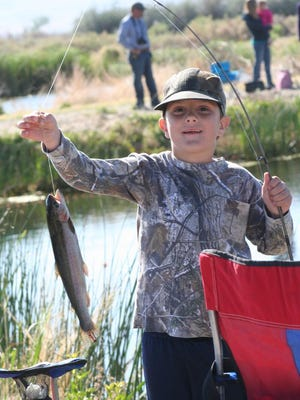 This boy shows off the trout he caught during the 2013 Mason Valley Kids' Fish Day at the settling ponds at the Mason Valley Fish Hatchery.