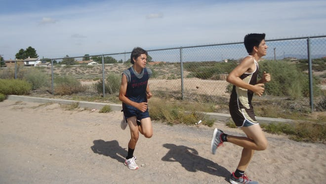 Rhavi Giovannetti, left, picked up the pace during Saturday's Santa Teresa Invitational Cross Country Meet in Anthony, N.M.