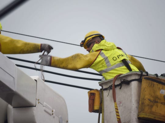 PSE&G workers on Route # 46 East, the scene of pole and wires down across the highway..