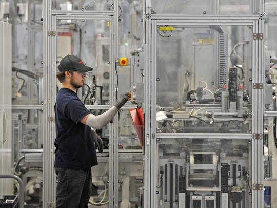 A worker checks a control panel at Nissan's battery plant in Smyrna.