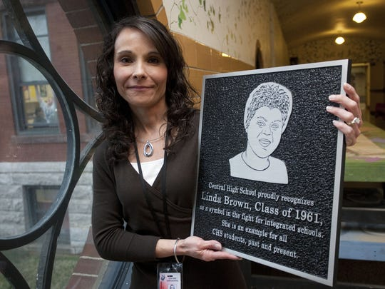 Central High Principal Lisa Anderson holds a plaque commemorating the 50th anniversary of Linda Brown's graduating class at Central in 2011. Brown's family was the namesake of the landmark Civil Rights case that desegregated schools.