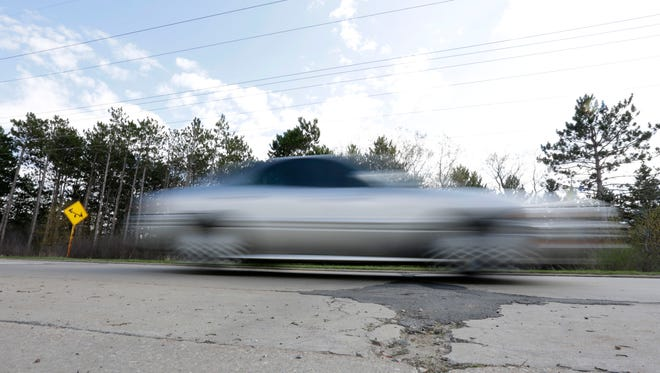 A car flies by along W 29th Street, which has some of the city's most substantial potholes, April 21, 2016.