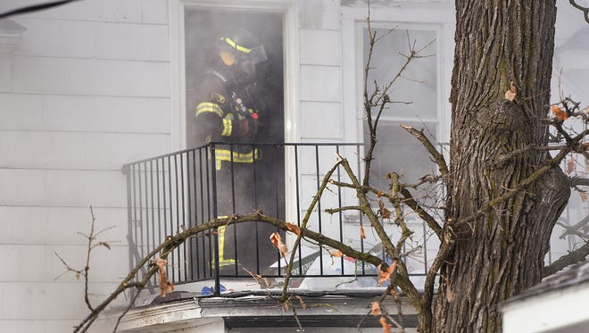 St. Cloud firefighters search the burning apartment house for occupants Tuesday, Dec. 27 at 814 Sixth Ave. S.