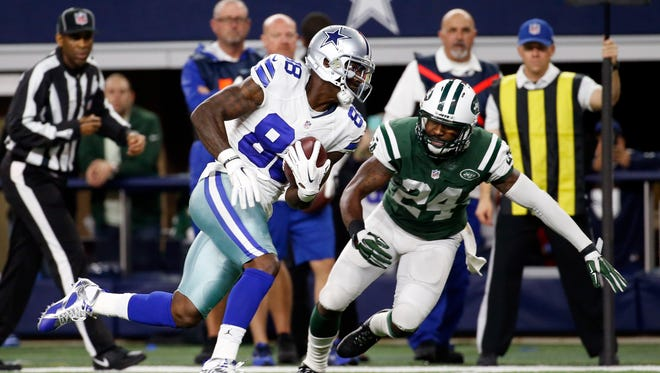 Dallas Cowboys wide receiver Dez Bryant (88) runs past New York Jets cornerback Darrelle Revis (24) for a touchdown during the first half at AT&T Stadium.