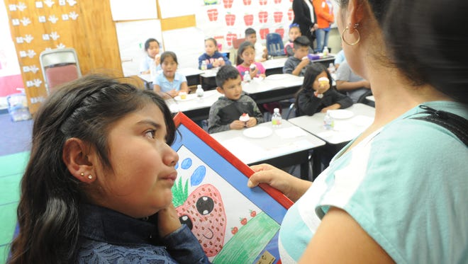 Allison Chavez, 8, a second-grader at Art Haycox School, is shown with her mother, Edelia Guzman, Monday after her entry was selected the winner of the California Strawberry Festival Youth Art Design Contest.