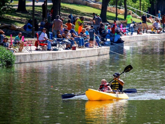 A crowd gathers along the Concho River in downtown
