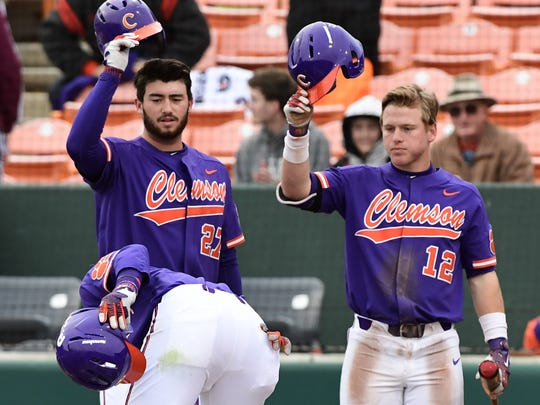 Clemson teammates Chris Williams(27) left, and Robert Jolly congratulate first baseman Seth Beer (28) at home plate after he hit a home run against William and Mary during the bottom of the third inning on Saturday at Doug Kingsmore Stadium in Clemson.