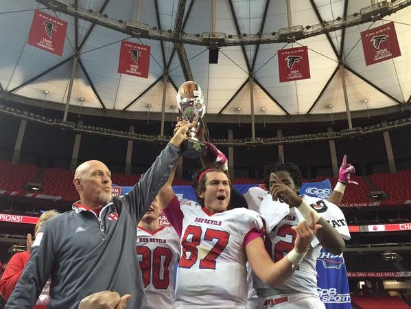 Hawkinsville coach David Daniell and players holding up their new trophy.