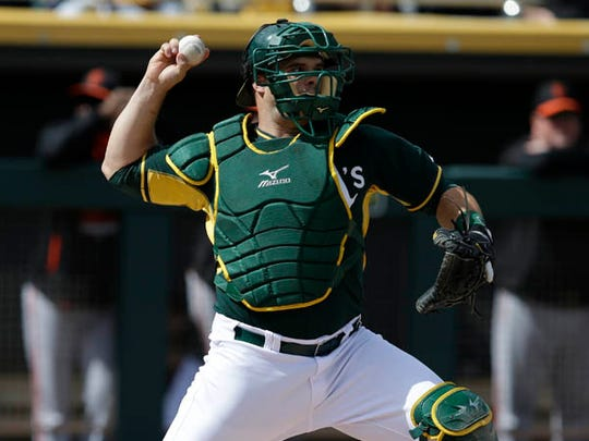 Oakland Athletics' Josh Phegley (19) throws during a spring training baseball game against the San Francisco Giants Tuesday, March 3, 2015, in Mesa, Ariz. (AP Photo/Darron Cummings)