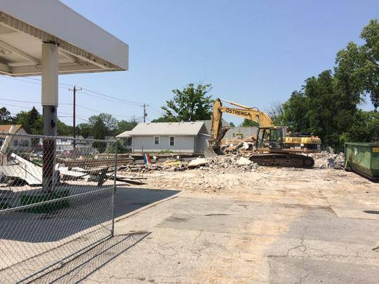 Crews demolish the old gas station at East Mason and Bellevue streets on July 2.