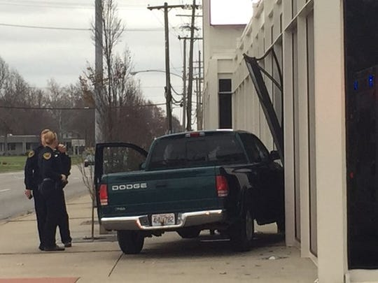 A green Dodge pickup has struck the side of the Central Bank building on Sunshine Street, east of Glenstone Avenue.
