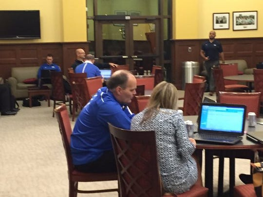 Inside the recruiting center at UWF Argo Athletic Club where UWF football staff are hovered over computers.