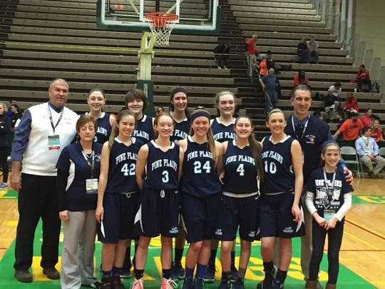 The Pine Plains girls basketball team poses for a photo after winning a state semifinal game on March 12.