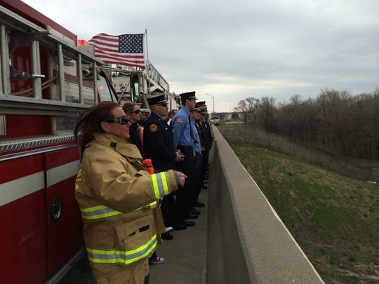 A long line of service men and women line the Meredith bridge over Interstate Highway 80/35 and await the funeral procession for fallen Des Moines police officer Susan Farrell on Wednesday, March 30, 2016.