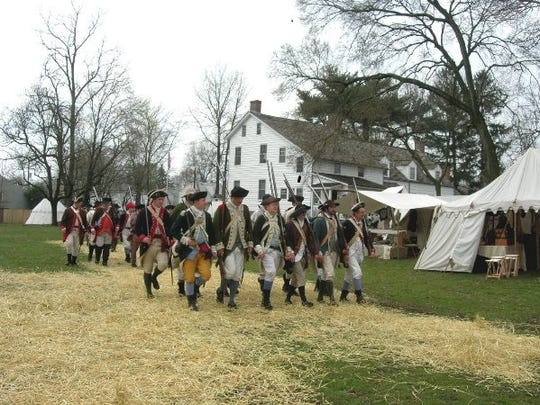 Continental soldiers march by the sutlers' tents on the grounds of the Abraham Staats house, 17 von Steuben Lane,  South Bound Brook.