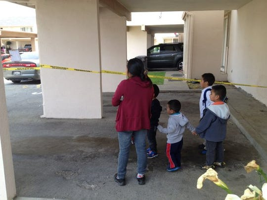 A woman and several children wait for police to allow them back in their home at the Acosta Plaza homicide crime scene in Salinas.